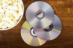 Immagine di popcorn in una ciotola ed in CD. immagine stock libera da diritti