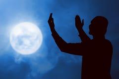 Immagine di pregare dell'uomo della siluetta Immagine Stock