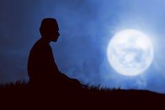 Immagine di pregare dell'uomo della siluetta Fotografia Stock