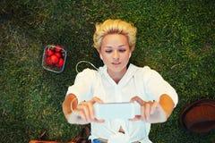 Immagine di presa femminile affascinante dei capelli biondi con il telefono delle cellule durante il resto in un prato Immagine Stock