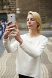 Immagine di presa turistica femminile splendida con il suo smartphone mentre stando all'aperto in via della città Fotografia Stock