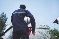 Immagine di priorità alta della sfuocatura dell'ingegnere asiatico nel holdin dell'uniforme di sicurezza Immagini Stock Libere da Diritti