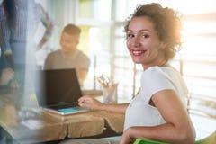 Immagine di riuscita donna casuale di affari che per mezzo del computer portatile nel corso della riunione fotografia stock libera da diritti