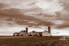 Immagine di seppia di una casa antiquata dell'azienda agricola di Amish con 2 silos in Pensilvania rurale, la contea di Lancaster immagini stock libere da diritti