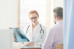 Immagine di sorveglianza sorridente dei raggi x del pulmonologist fotografia stock