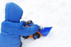 Immagine di un bambino che si siede sulla neve bianca e che gioca con un giocattolo ex fotografia stock