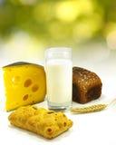 Immagine di un bicchiere di latte, pane sul primo piano del bordo, del grano e del formaggio fotografia stock libera da diritti