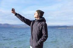 Immagine di un giovane che prende un selfie con il suo telefono fotografia stock libera da diritti