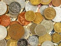 Immagine di un gran numero di monete dei vecchi soldi dei paesi differenti sul fondo del dollaro fotografia stock libera da diritti
