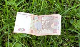 Immagine di una banconota ucraina di Hryvnia su un fondo dell'erba Immagini Stock Libere da Diritti