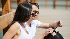 Immagine di una coppia allegra facendo uso degli smartphones nel parco archivi video