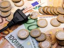 Immagine di una spina di corrente dentro e monete e fatture dei soldi dell'euro fotografie stock