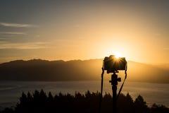 Immagine di viaggio di una messa a punto della macchina fotografica per sparare tramonto sopra una collina in Nuova Zelanda fotografia stock