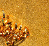 Immagine di vista superiore del nastro dorato riccio sopra il fondo strutturato di scintillio Fotografia Stock