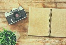 Immagine di vista superiore del taccuino in bianco e di vecchia macchina fotografica Retro filtrato Fotografia Stock