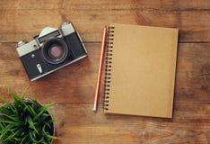 Immagine di vista superiore del taccuino in bianco e di vecchia macchina fotografica Retro filtrato Fotografie Stock