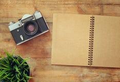 Immagine di vista superiore del taccuino in bianco e di vecchia macchina fotografica Retro filtrato Immagini Stock Libere da Diritti