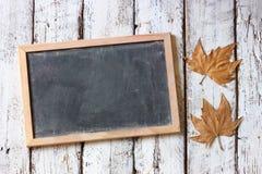 Immagine di vista superiore delle foglie di autunno accanto alla lavagna sopra fondo strutturato di legno Copi lo spazio Fotografia Stock