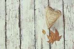 Immagine di vista superiore delle foglie di autunno e del cuore del tessuto sopra fondo strutturato di legno Copi lo spazio Fotografia Stock Libera da Diritti
