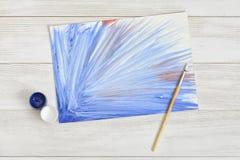 Immagine dipinta con i barattoli di plastica di pittura blu e bianca sulla tavola di legno Immagini Stock Libere da Diritti