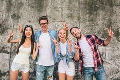 Immagine divertente dei ragazzi felici e positivi e di girlsstanding sul fondo e sulla posa grigi Stanno mostrando il simbolo del Fotografie Stock Libere da Diritti