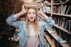 Immagine divertente della ragazza che sta scaffale per libri vicino Sta tenendo due libri sulla sua testa con le sue mani e sta g Immagine Stock Libera da Diritti