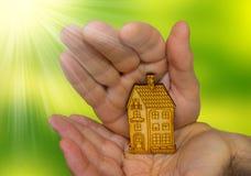 Immagine luminosa dell'uomo che tiene casa di legno Immagine Stock