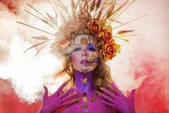 Immagine luminosa di Halloween, stile messicano con i crani dello zucchero sul fronte Pelle rosa luminosa della giovane bella don fotografia stock