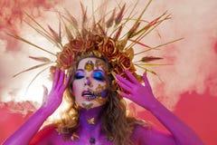 Immagine luminosa di Halloween, stile messicano con i crani dello zucchero sul fronte Pelle rosa luminosa della giovane bella don fotografia stock libera da diritti
