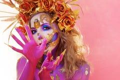 Immagine luminosa di Halloween, stile messicano con i crani dello zucchero sul fronte Pelle rosa luminosa della giovane bella don immagine stock libera da diritti