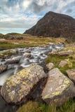 Immagine lunatica del paesaggio del fiume che scorre giù la catena montuosa vicino fotografia stock