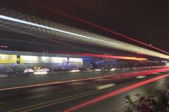 Immagine lunga di esposizione delle automobili che precipitano sopra una strada principale Immagini Stock