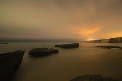 Immagine lunga di esposizione delle rocce costiere sulla spiaggia dell'oceano Immagini Stock Libere da Diritti