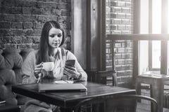 immagine monocromatica La giovane donna con capelli lunghi si siede alla tavola vicino alla finestra in caffè, caffè bevente e sm Fotografia Stock