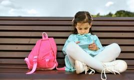 Immagine orizzontale di aria aperta della ragazza del bambino che gioca con lo smartphone che si siede sul banco nel parco della  fotografie stock