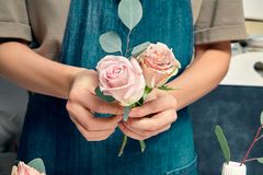Immagine potata del fiorista femminile sul lavoro Organizzazione dei fiori vari in mazzo Fiori alti vicini a disposizione Posto d immagini stock