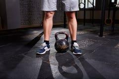Immagine potata del giovane, delle gambe in breve e del kettlebell Tema di allenamento di Crossfit su fondo grigio Fotografia Stock