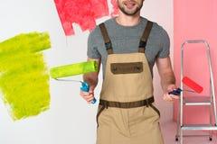 immagine potata dell'uomo nel lavoro complessivo con i rulli di pittura fotografie stock libere da diritti