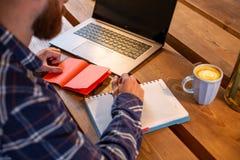 Immagine potata dell'uomo o delle free lance casuale di affari che progetta il suo lavoro sul taccuino, lavorante al computer por Fotografia Stock
