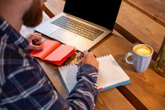 Immagine potata dell'uomo o delle free lance casuale di affari che progetta il suo lavoro sul taccuino, lavorante al computer por Fotografie Stock