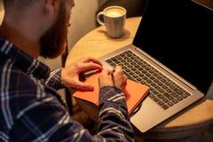 Immagine potata dell'uomo o delle free lance casuale di affari che progetta il suo lavoro sul taccuino, lavorante al computer por Immagine Stock