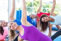 Immagine potata delle donne allegre che fanno allungamento laterale Immagini Stock