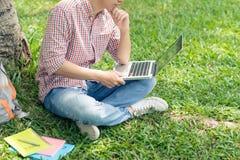 Immagine potata dello studente che si siede sul prato inglese del parco e che lavora al rivestimento Fotografie Stock