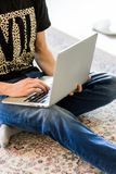 Immagine potata di un giovane che lavora al computer che si siede alla tavola di legno immagine stock