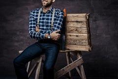 Immagine potata Lavoratore, carpentiere, uomo del tuttofare che porta una camicia a quadretti con le bretelle che si siedono su u immagine stock libera da diritti