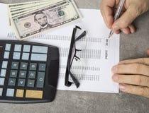 Immagine profitti e perdite di concetto di una penna, di un calcolatore e delle monete sui documenti finanziari immagine stock