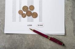 Immagine profitti e perdite di concetto di una penna, di un calcolatore e delle monete sui documenti finanziari immagini stock libere da diritti
