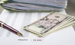 Immagine profitti e perdite di concetto di una penna, di un calcolatore e delle monete sui documenti finanziari immagine stock libera da diritti