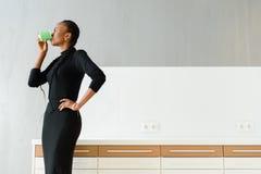 Immagine schietta di un caffè bevente della donna di affari mentre lavorando all'ufficio leggero Fotografie Stock