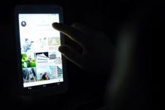 Immagine scura dell'uomo che usando applicazione del instagram sul suo cuscinetto di tocco Fotografia Stock